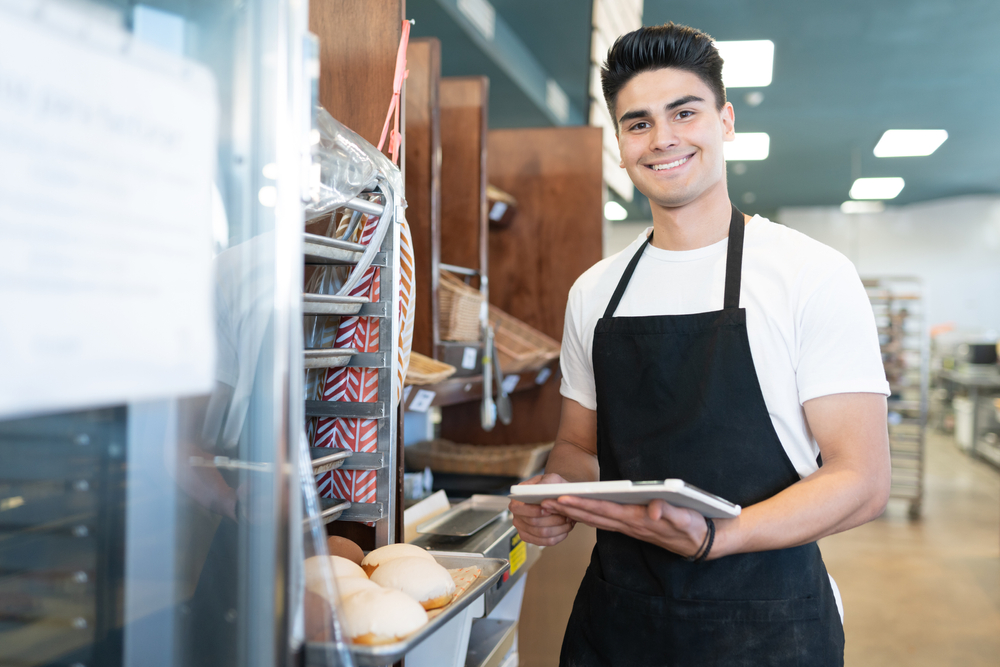bakery employee holds ipad with self ordering software