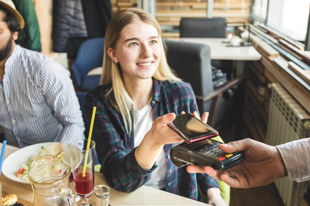 woman in restaurant pays using mpos