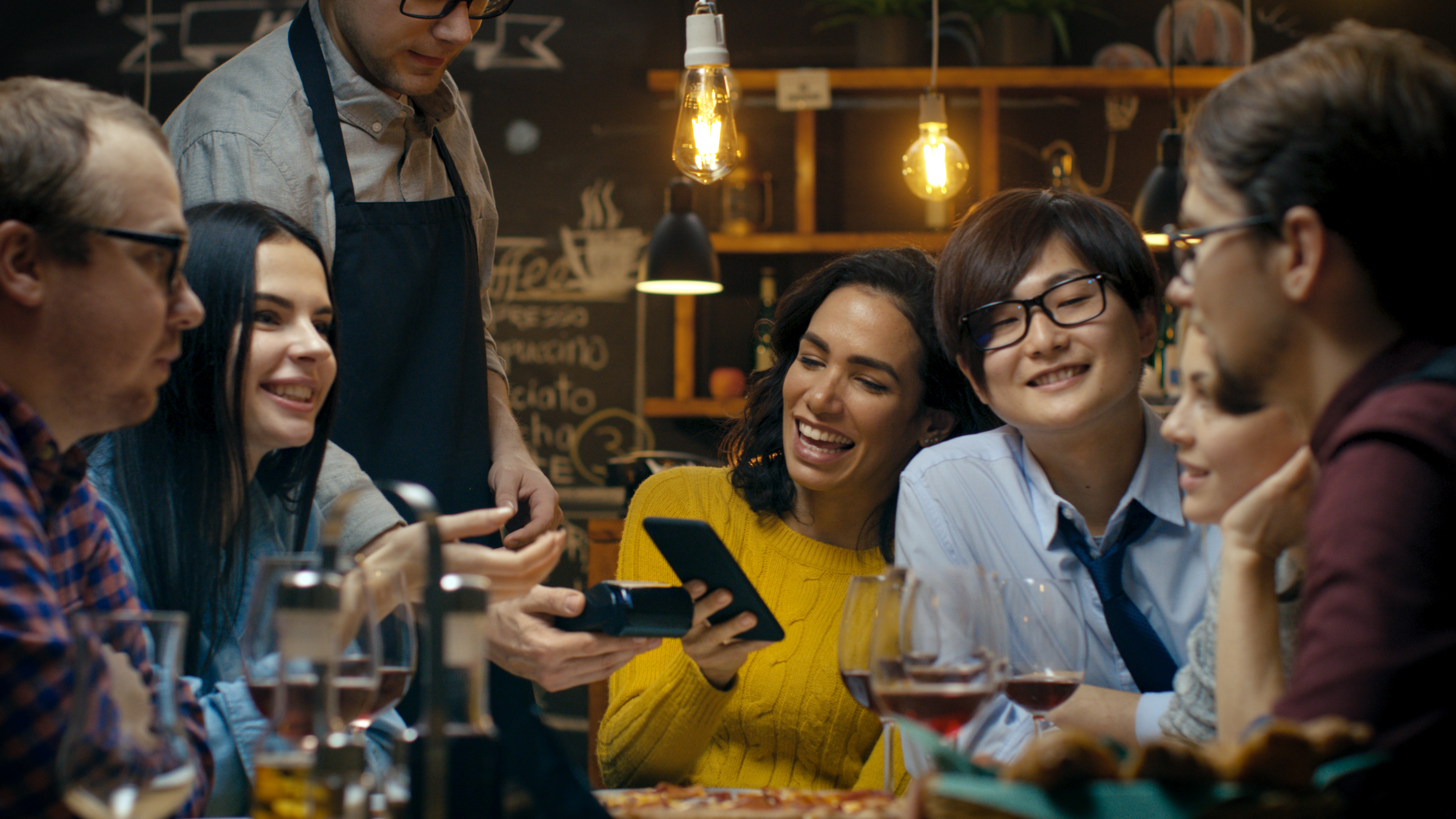Customers at cafe use mobile sales system for payment