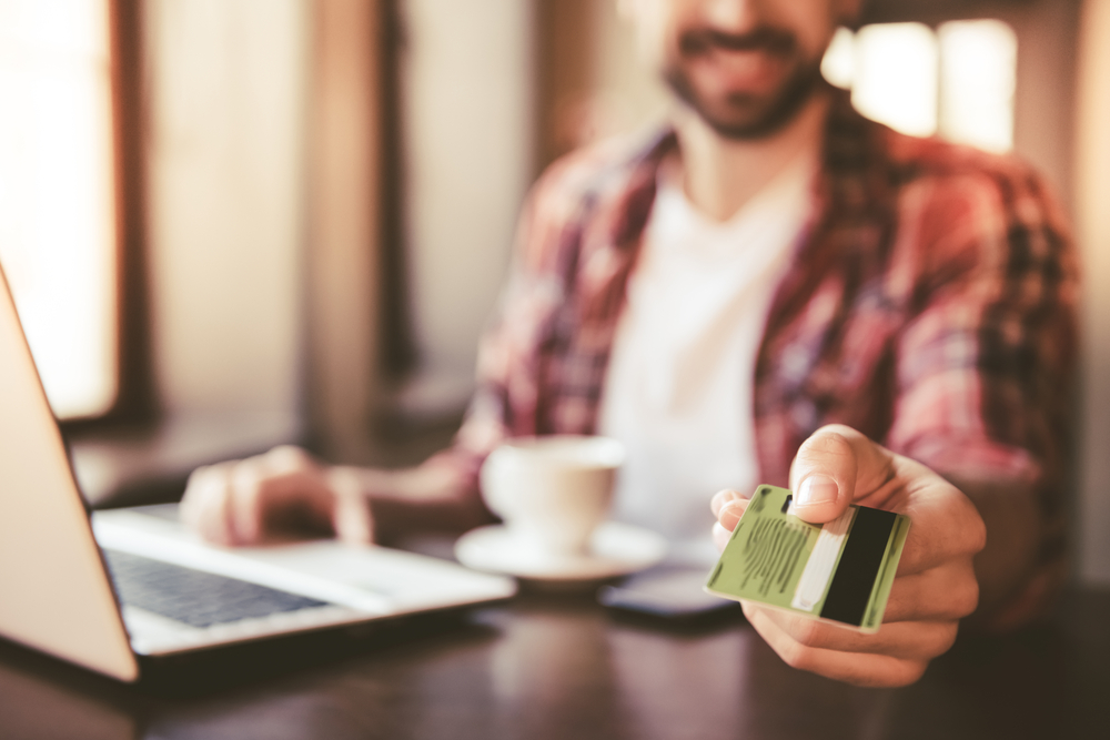 man in cafe hands credit card to employee