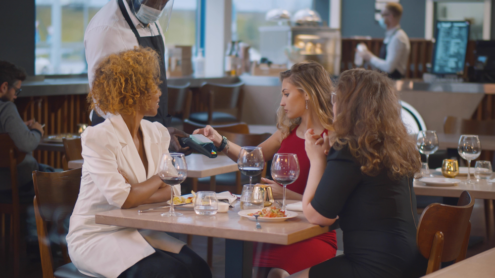 diners at restaurant pay with contactless card