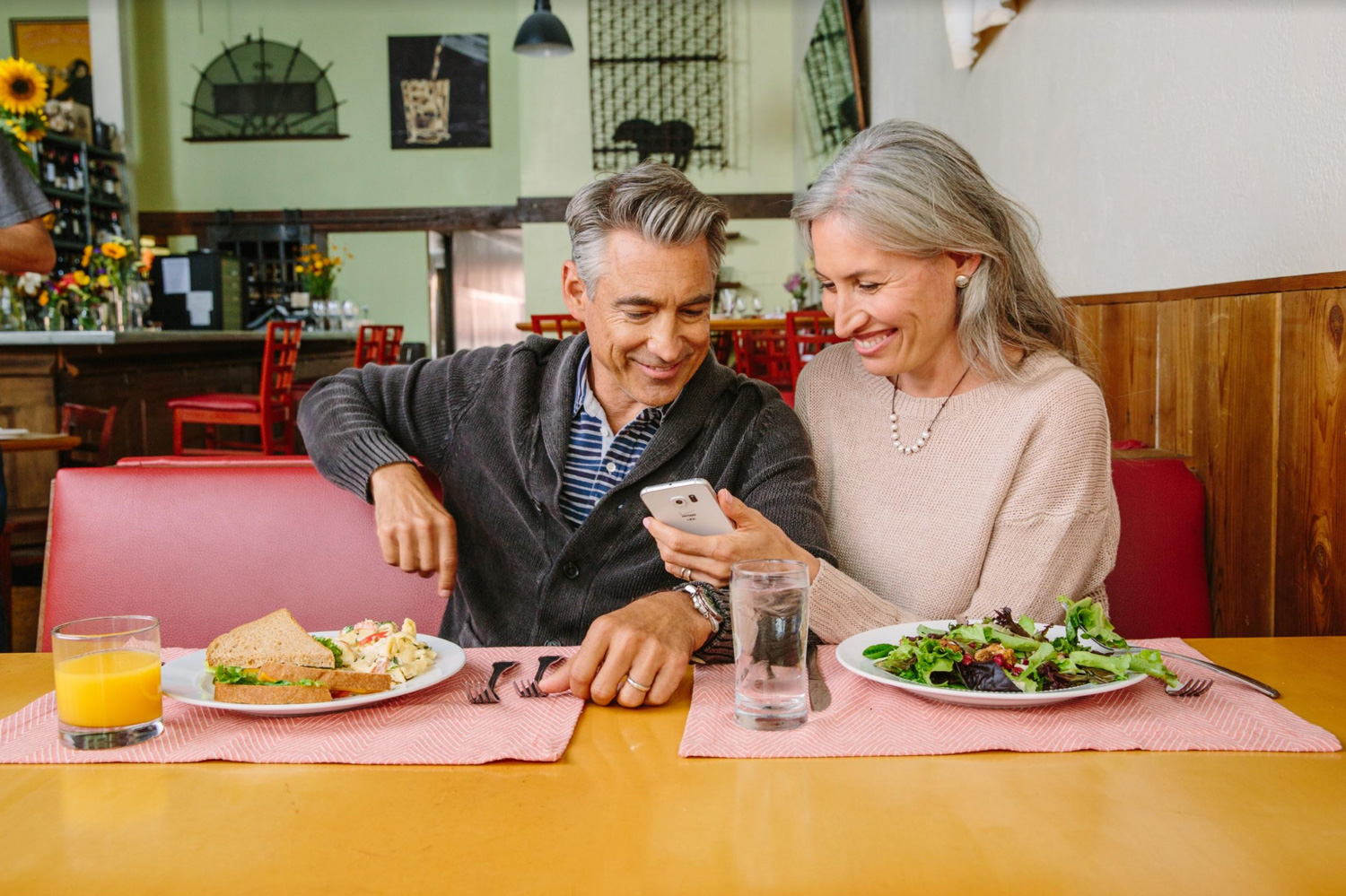 A couple look at a mobile phone while having a meal in a restaurant
