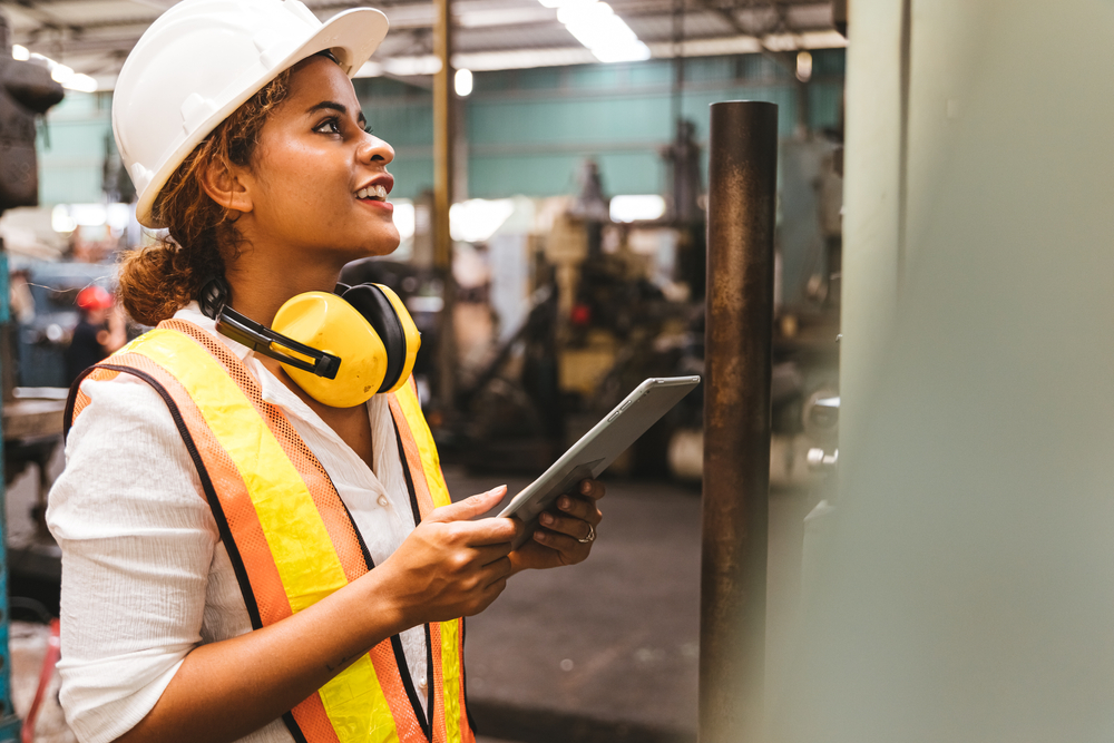 worker examines wall while holding ipad