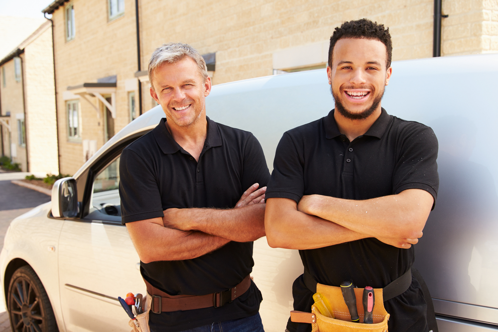 two tradesmen stand near van and smile
