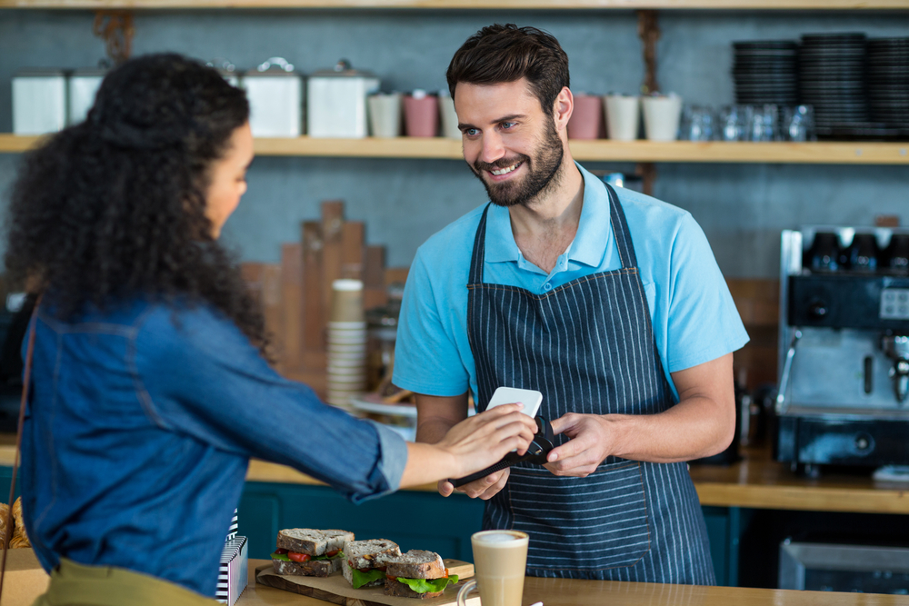 employee in cafe accepts mpos payment from customer