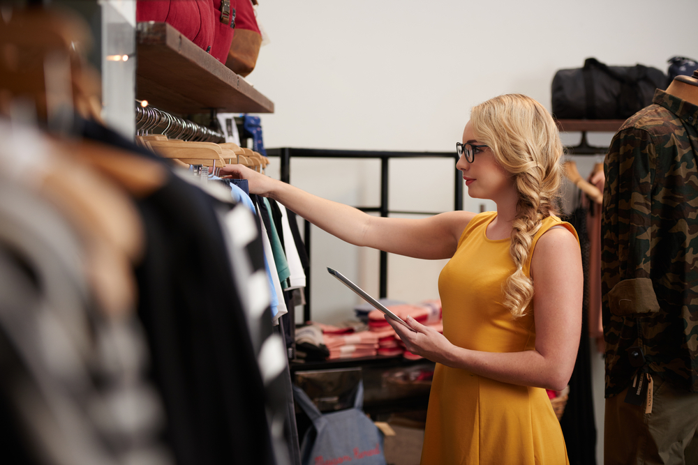 shop employee tracks clothing inventory on tablet pos