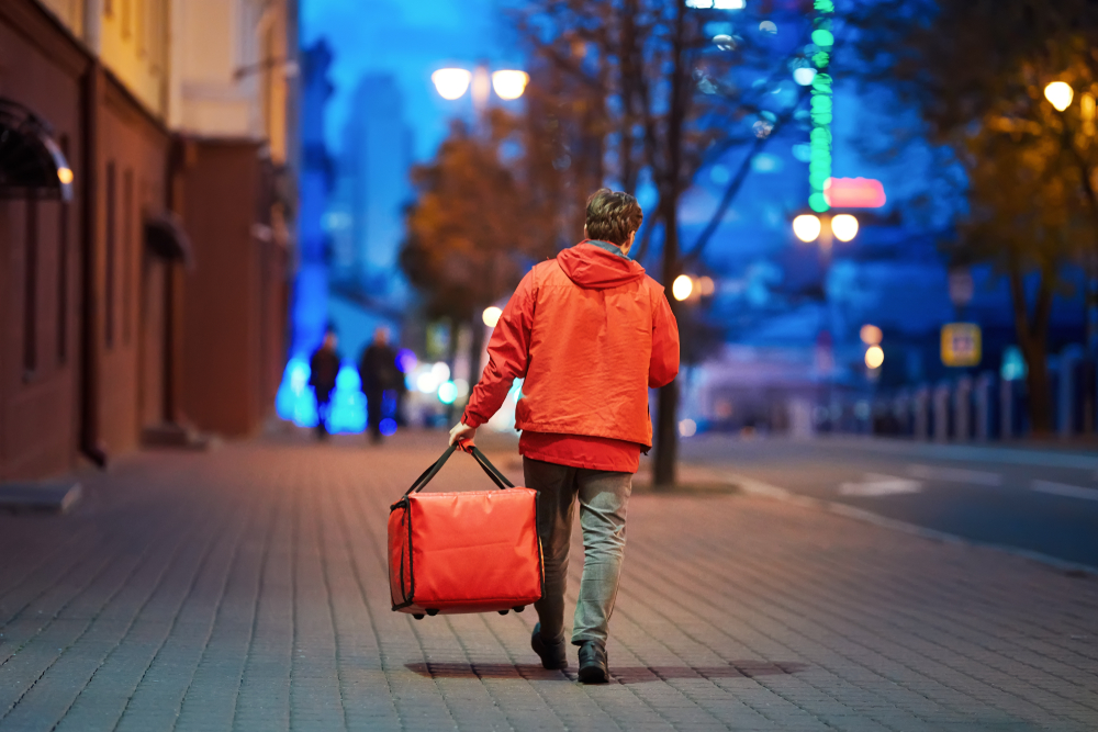 Delivery person carries a bag on the way to a customer