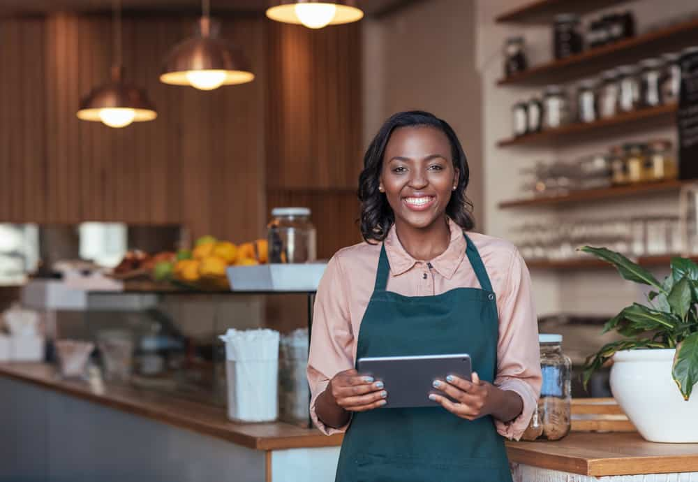 Businesswoman smiles while holding a tablet