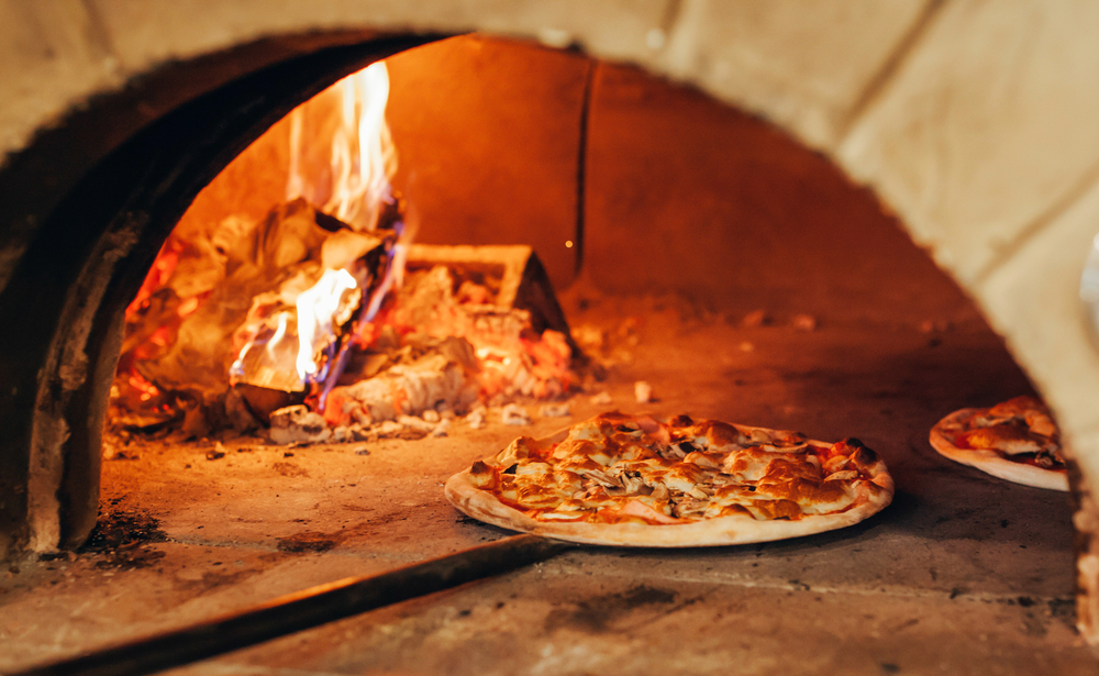 Pizzas cooking in a wood-fired oven