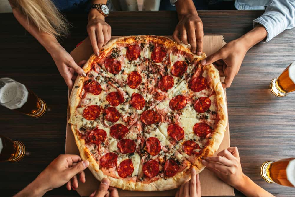 Hands reaching for slices of pizza