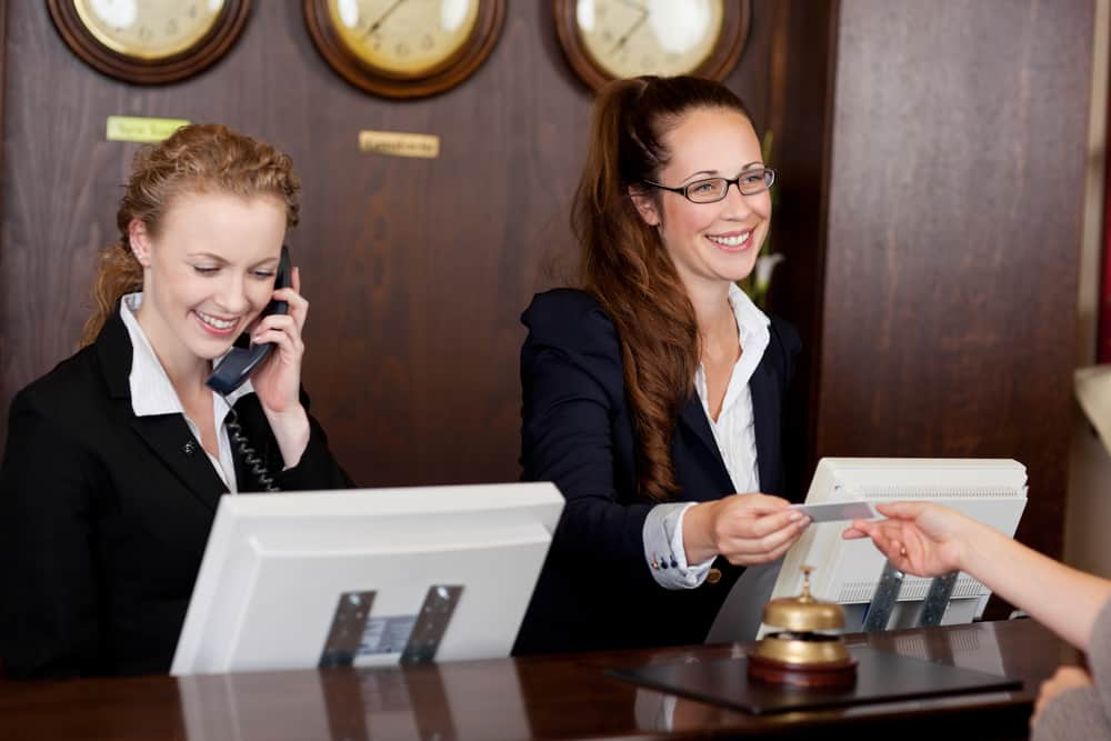 Two women help customers at a hotel desk
