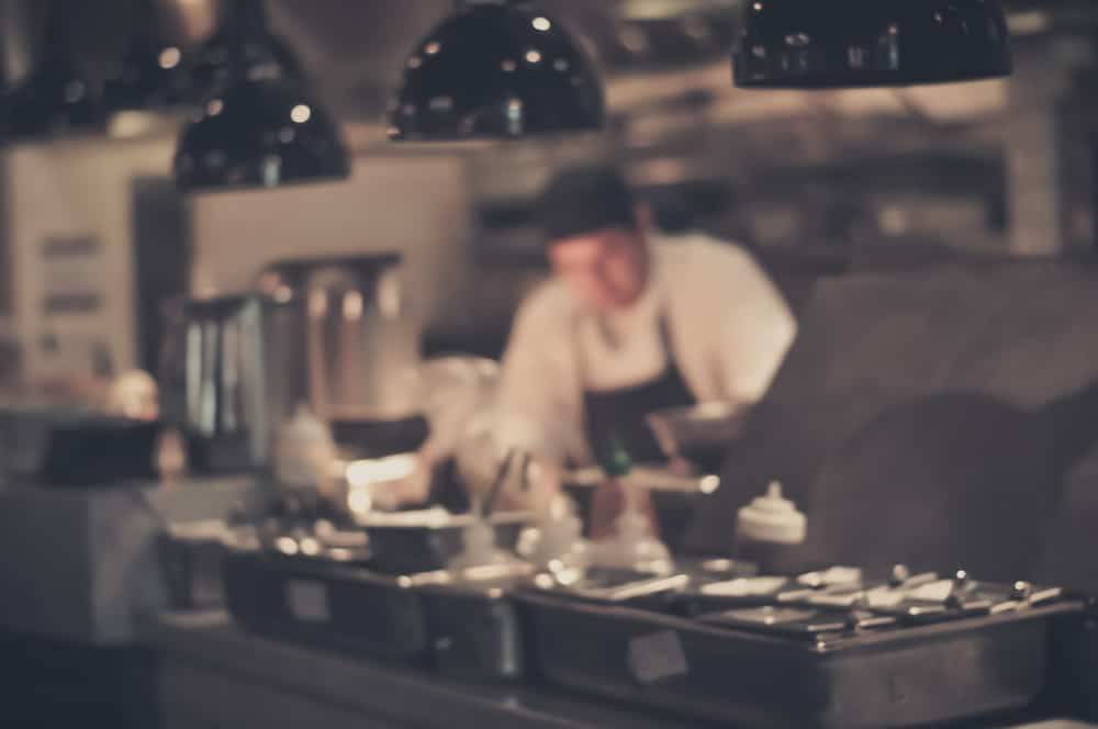 Blurred image of a chef in restaurant kitchen