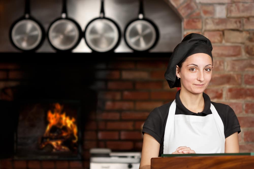 Pizza chef stands in front of a brick oven
