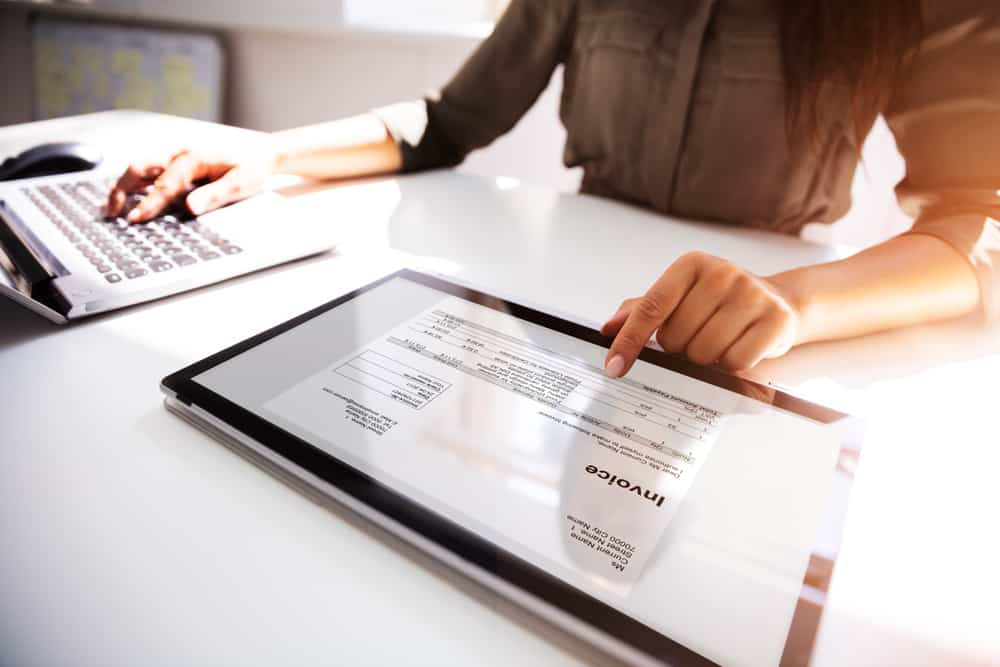 Business owner reviews invoices on their laptop and tablet.