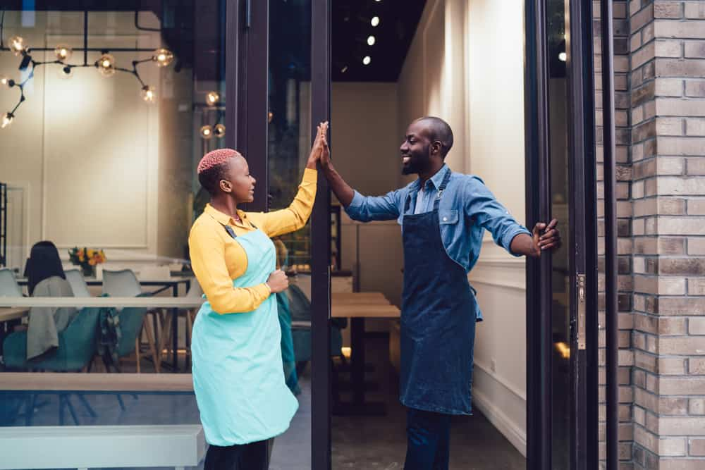 Two business owners high five as they open their restaurant