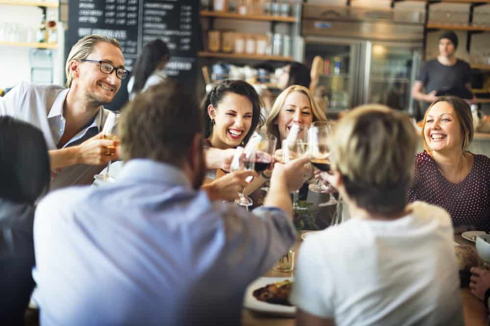 """A group of friends """"cheers"""" to a night out at a restaurant."""