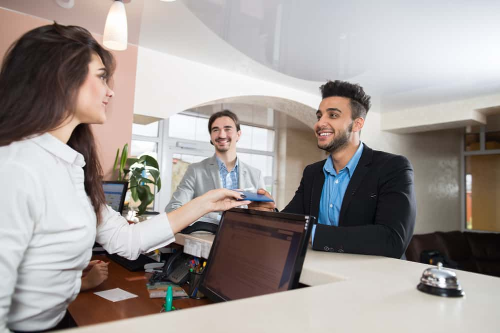 Two men checking into a hotel while a woman at the front desk helps