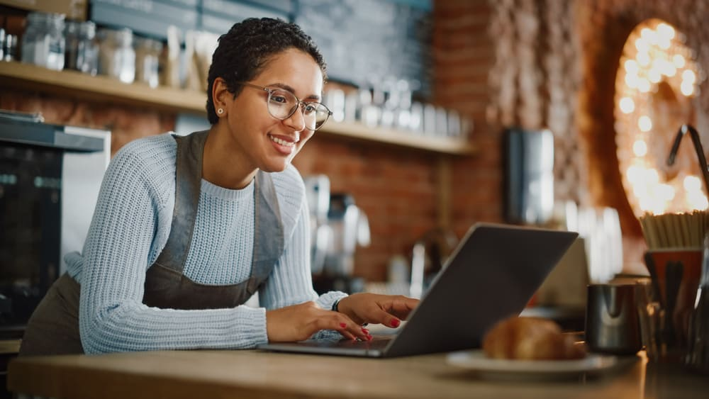 A business owner works on her laptop in her cafe.