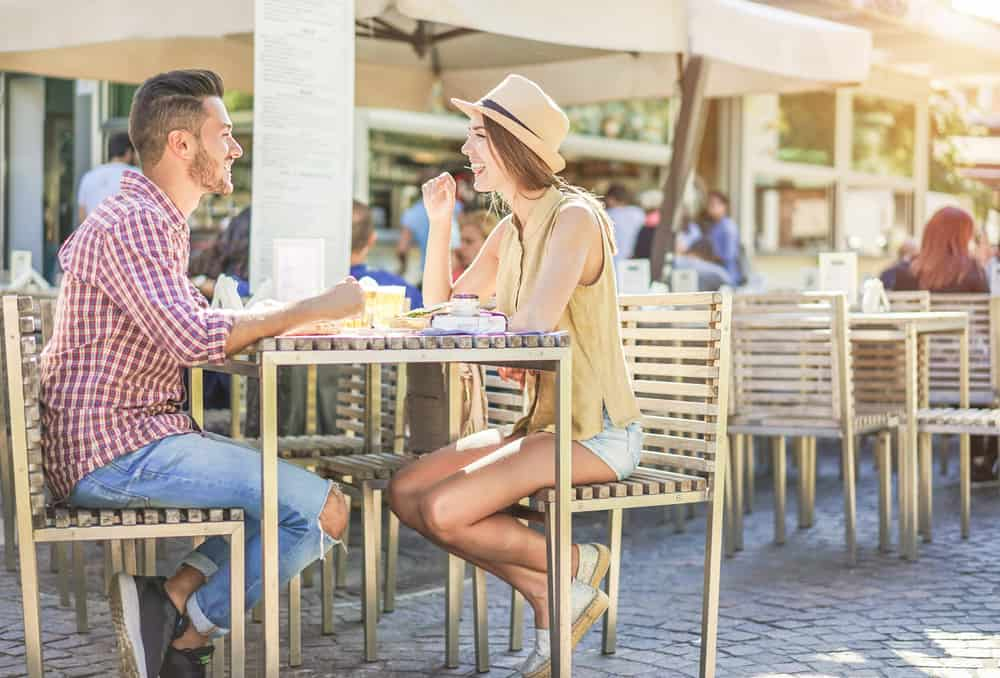 A couple enjoys eating outside at a restaurant during the summer.