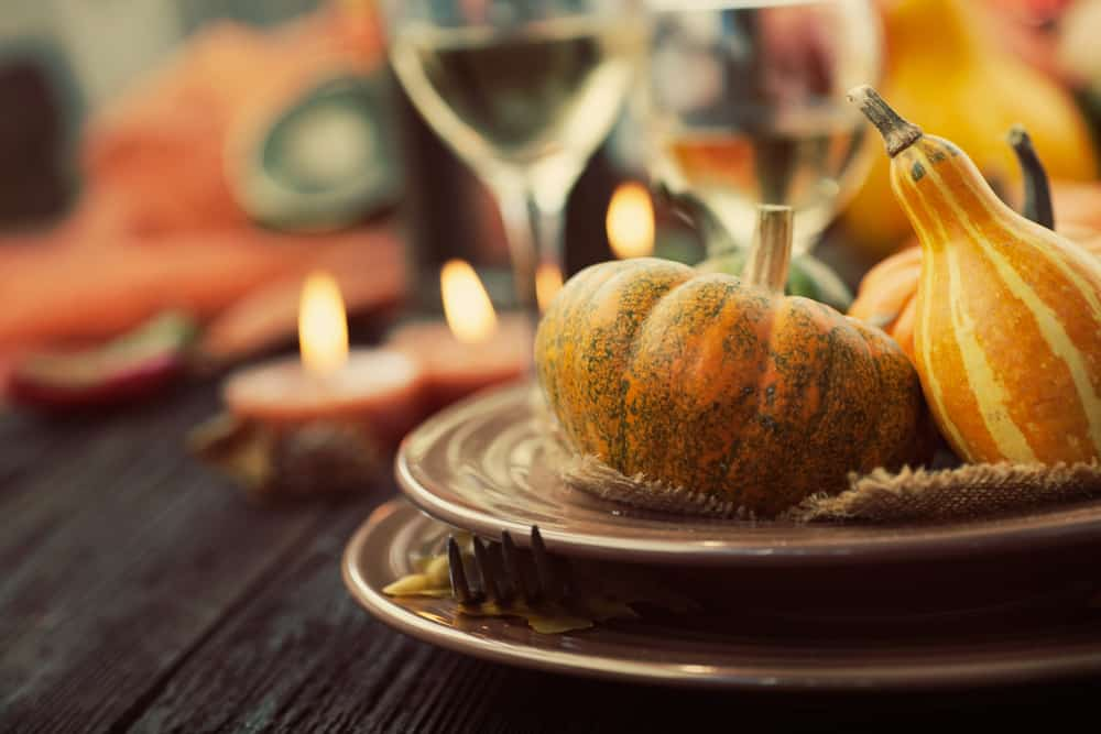 An autumnal themed place setting with wine, candles, and pumpkins