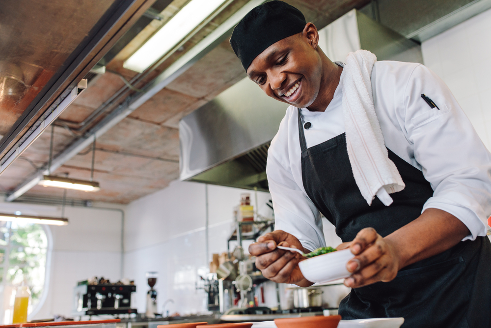 A chef in the kitchen focuses on seasoning his recipe.