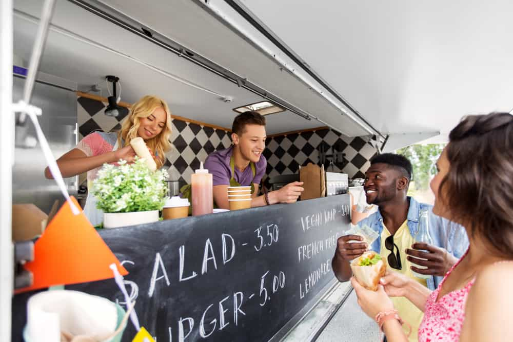 A smiling couple receives their order from a food truck.