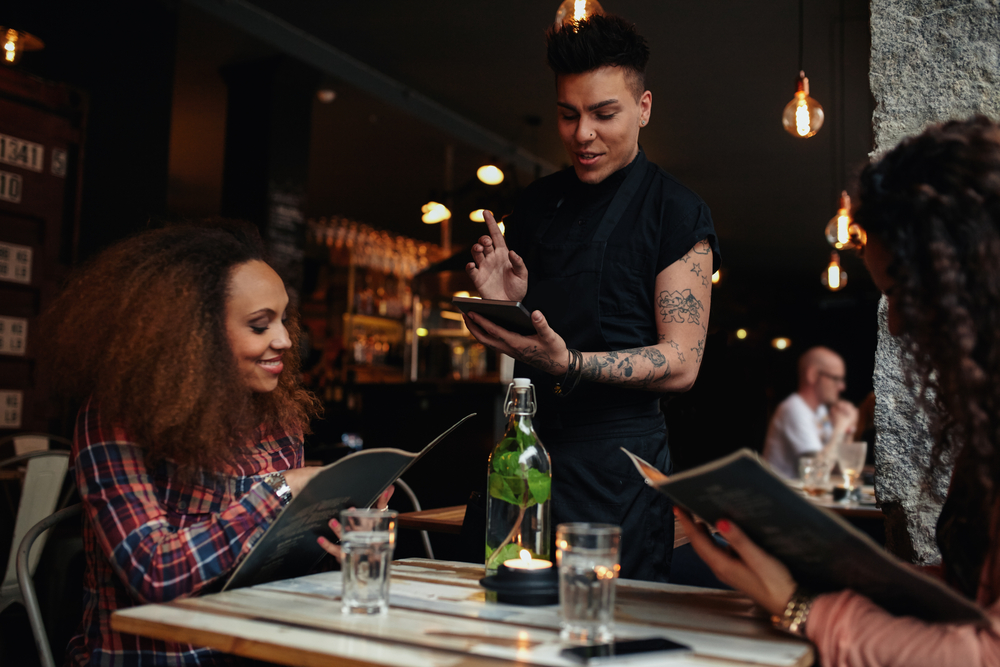 A young couple places their restaurant order with a waiter who is using a handheld tablet.