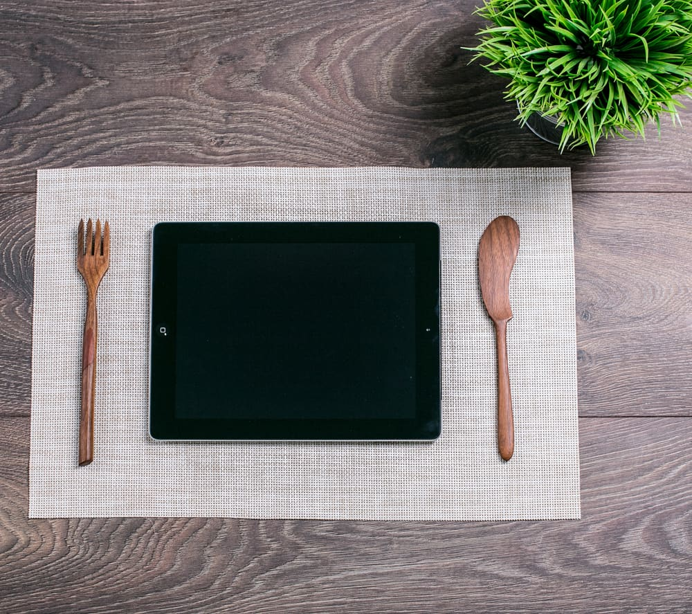 A tablet in the middle of a fork and knife on a table.