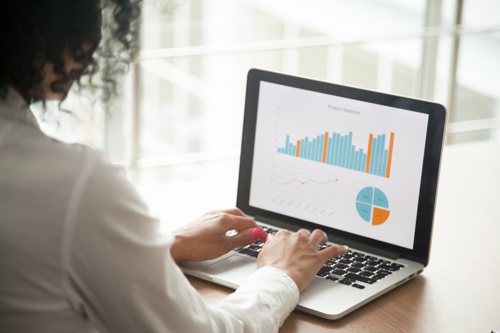 woman examines POS sales and marketing data on laptop