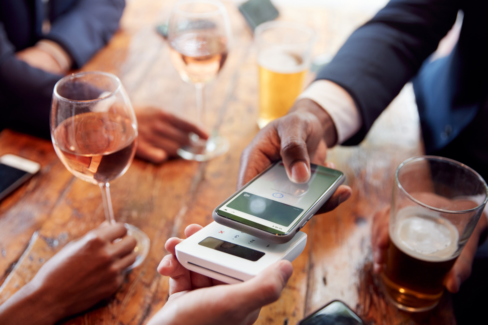 bar patron pays using contactless POS