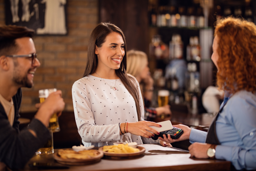 woman purchasing food and drinks at pub