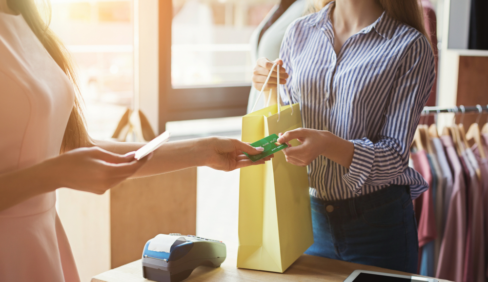 woman makes clothing purchase at retail store