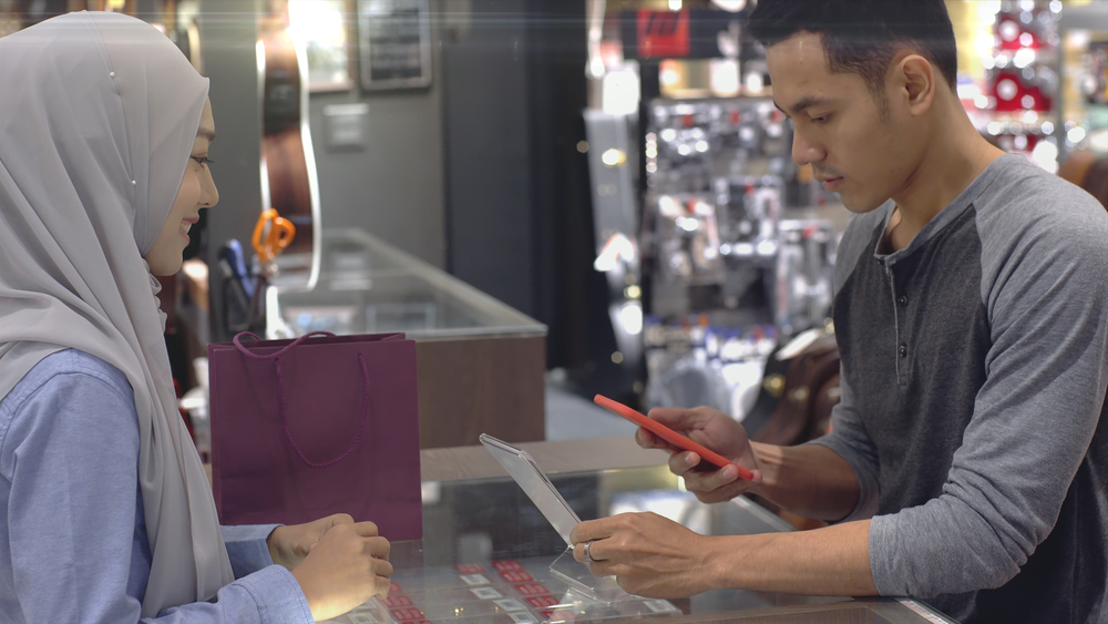 customer and employee look at iphone and ipad screen