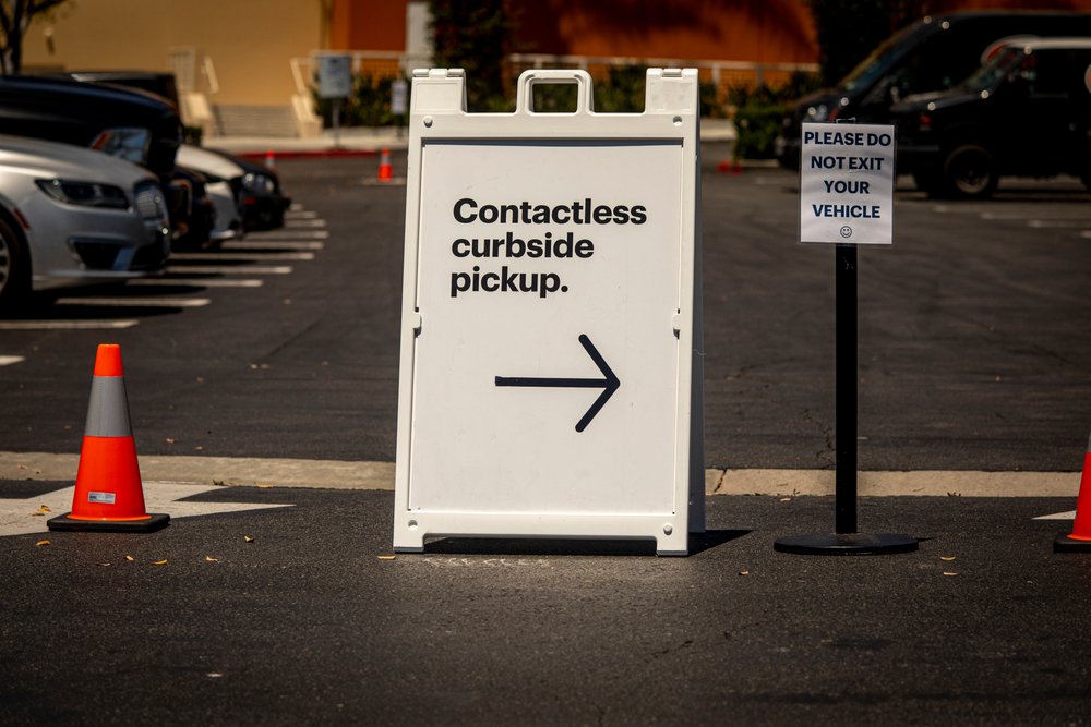 """sign in parking lot reading """"contactless curbside pickup"""" with arrow"""