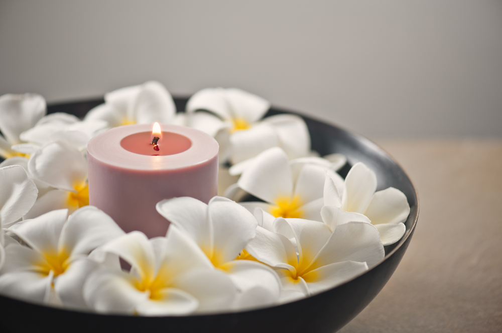 candle surrounded by flowers in spa