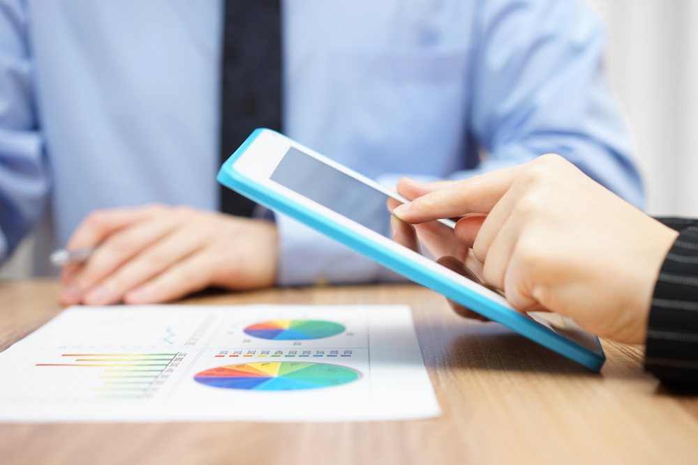 business people use ipad to examine pos data chart