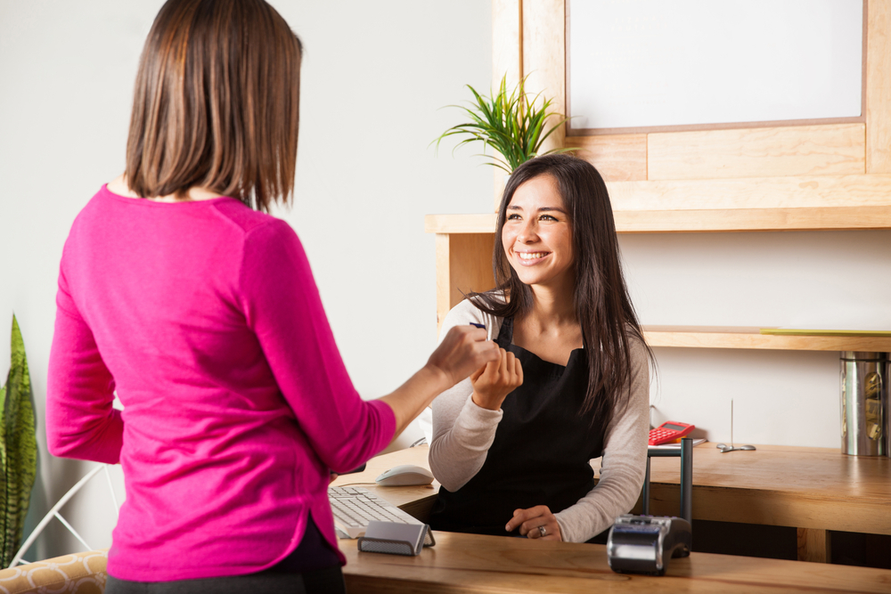 customer hands credit card to spa employee