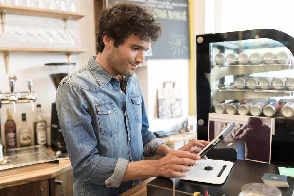 cafe employee makes sale on pos tablet