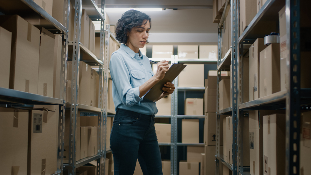 woman uses an ipad to track inventory in stock room