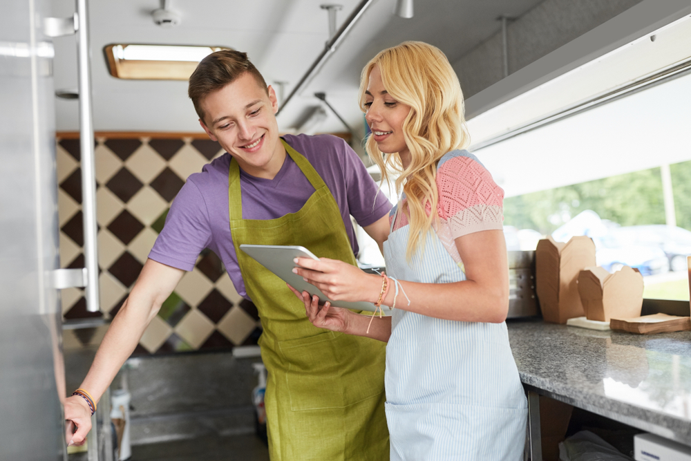 food truck owners discuss business matters while looking at pos tablet