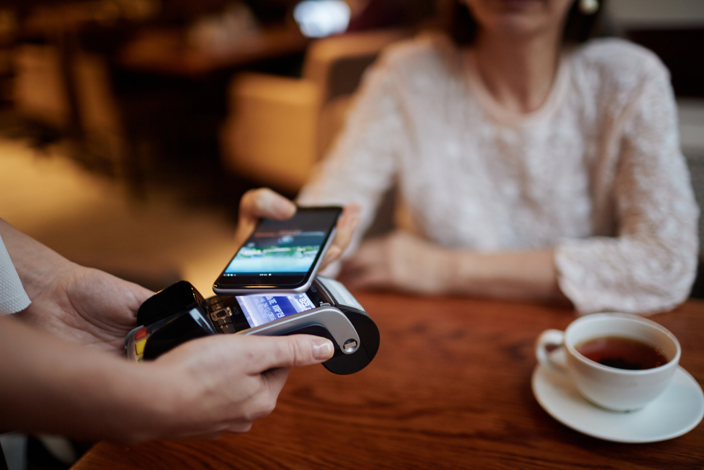 customer at cafe pays for tea with phone and contactless mobile pos terminal