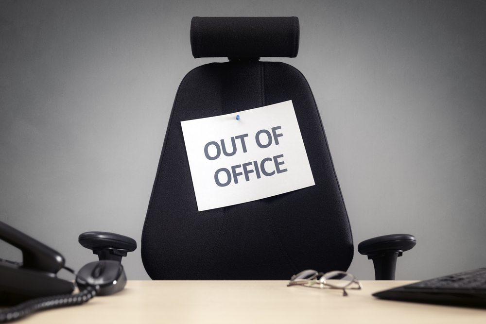"desk chair with a sign reading ""out of office"""
