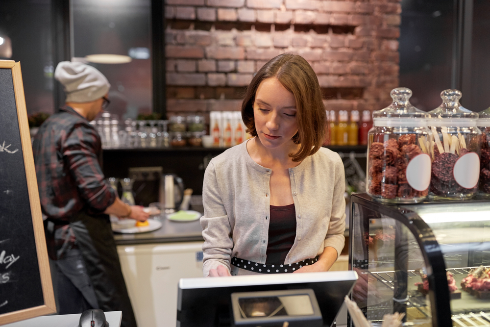 employee in cafe uses a pos system to process payments