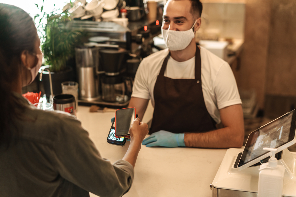 employee at cafe takes a digital cashless payment