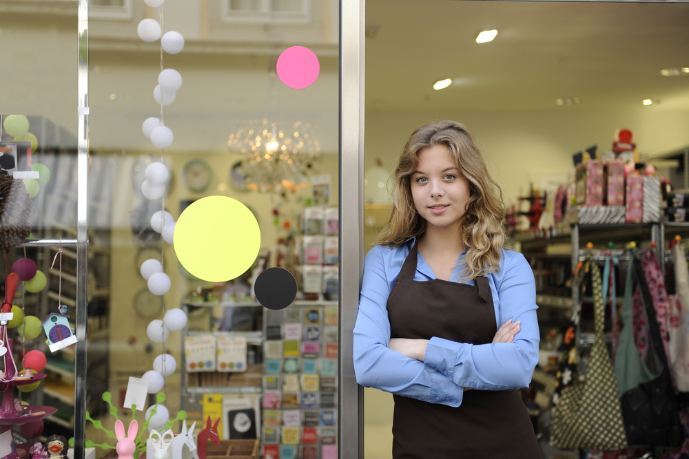 employee stands outside of shop